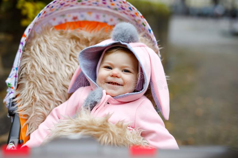 Cute little beautiful baby girl sitting in the pram or stroller on autumn day. Happy smiling child in warm clothes. Fashion stylish pink baby coat with bunny stock images