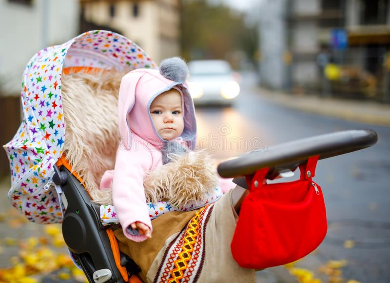 Cute little beautiful baby girl sitting in the pram or stroller on autumn day. Happy smiling child in warm clothes. Fashion stylish pink baby coat with bunny stock photo