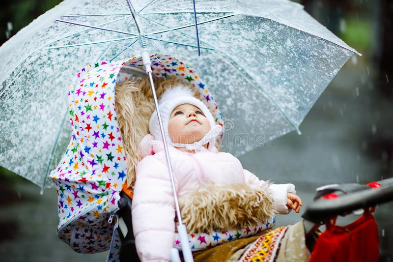 Cute little beautiful baby girl sitting in the pram or stroller on cold day with sleet, rain and snow. Happy smiling stock image