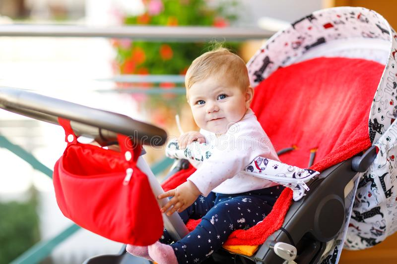 Cute little beautiful baby girl sitting in the pram or stroller and waiting for mom. Happy smiling child with blue eyes. Adorable baby daughter going for a stock images