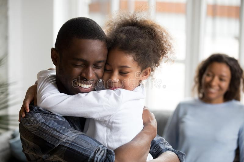 Cute little black girl embracing happy african american dad. At home, mixed race kid daughter and father hugging cuddling, daddy and child love care connection royalty free stock images