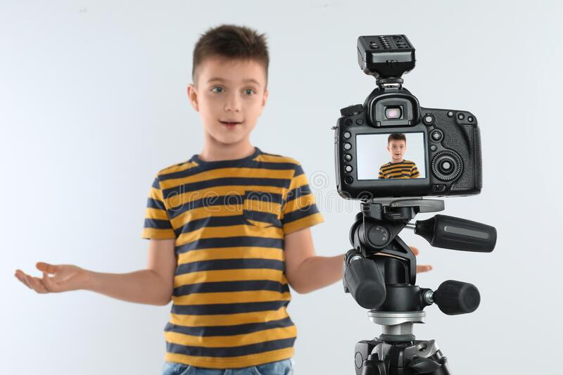 Cute little blogger recording video against white background, focus on camera stock images