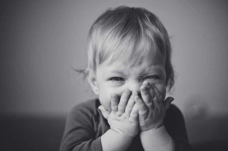 Cute little blond baby are bitterly cries and presses his hands to his face. Close up. royalty free stock photos