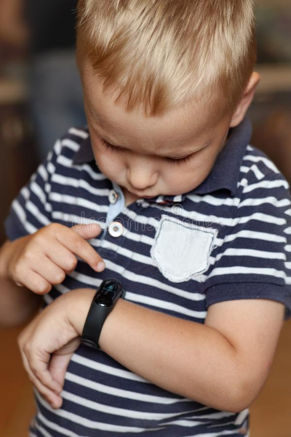 Cute little blond boy with blue eyes points out to digital fitness tracker on his wrist. royalty free stock photography