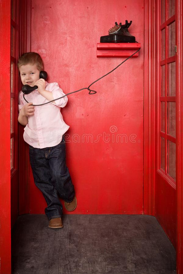 Cute little blond boy in a pink shirt and jeans call on the retro telephone in a British telephone box. old telephone royalty free stock photography