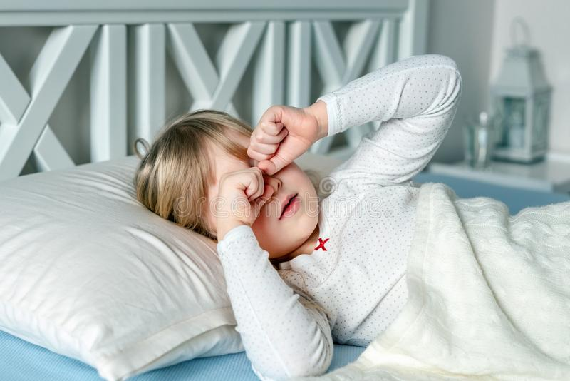 Cute little blond caucasian girl awakening at bed in morning. Child wake up early to go to school. Stretching and royalty free stock image