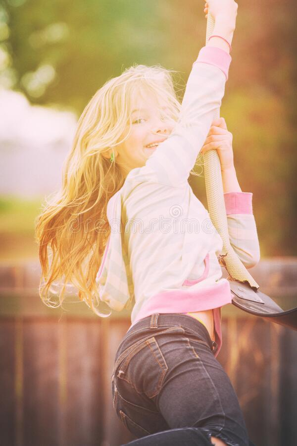 Laughing girl having fun on a swing at the playground stock photo