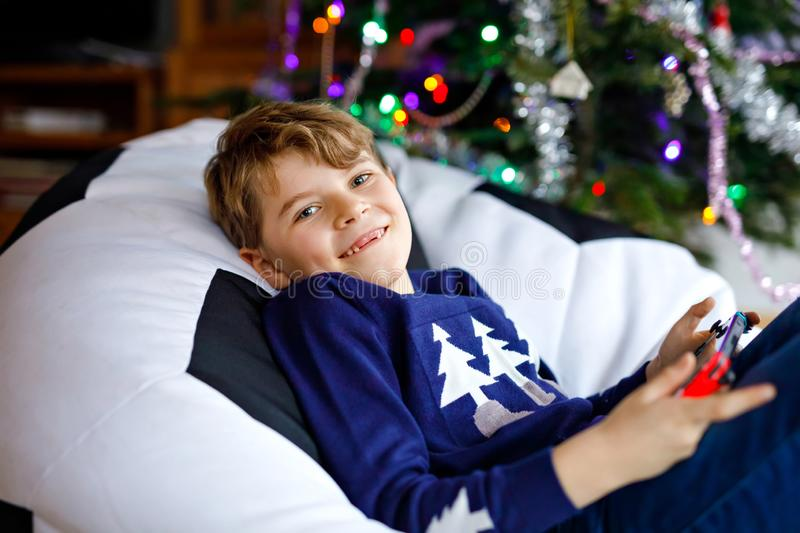Cute little blond kid boy playing with a video game on gadget console on Christmas with decorated tree on background royalty free stock photos