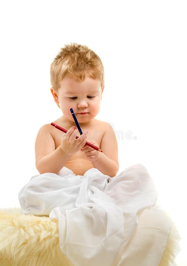 Cute little blond kid boy, three years old, sitting on a white background. royalty free stock image