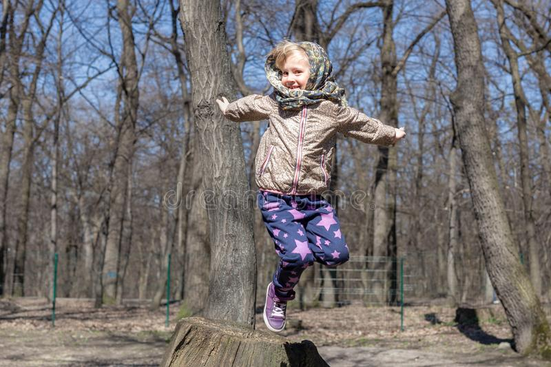 Cute little blond kid girl having fun outdoors. Child in casual sport wear and kerchief jumping high from tree stump in forest.  royalty free stock photos