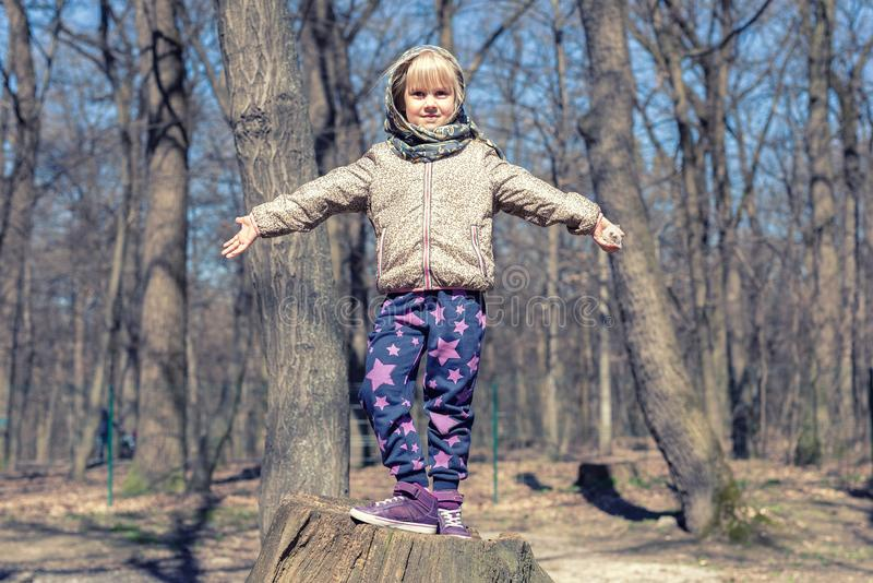 Cute little blond kid girl having fun outdoors. Child in casual sport wear and kerchief jumping high from tree stump in forest.  royalty free stock photo