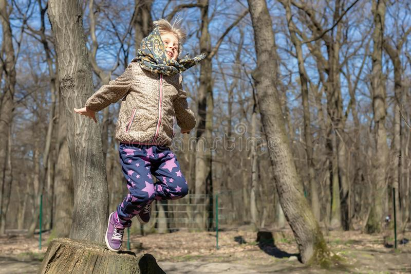 Cute little blond kid girl having fun outdoors. Child in casual sport wear and kerchief jumping high from tree stump in forest.  royalty free stock photography