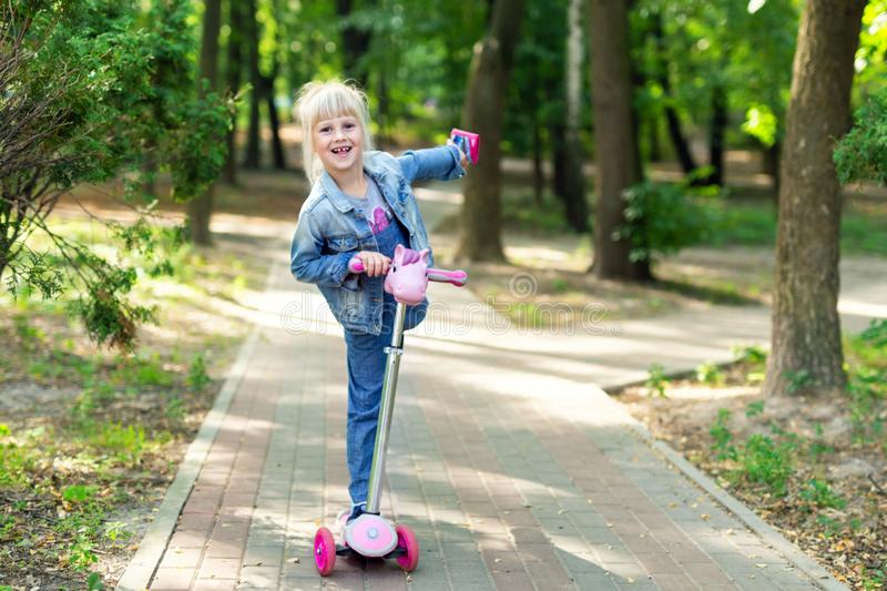 Cute little blond kid girl riding scooter in city park. Preschooler girl in jeans overall having fun during outdoor sport. Activities. Summer leisure and stock photography