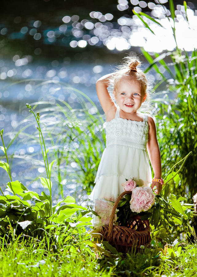 Cute little blonde girl is backlit against the background of wat stock photography
