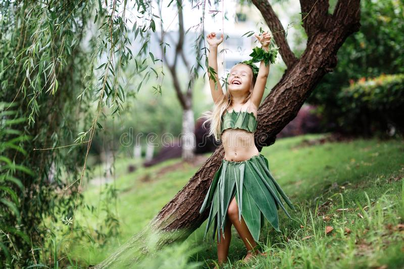 Cute little blonde girl in carnival costume made of green grass outdoor. Stylish kid ready for halloween party stock image