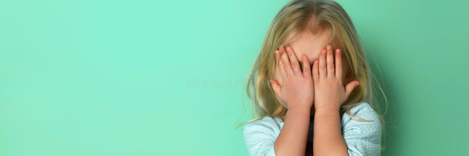 Cute little blonde girl covering his face for playing peekaboo, hide and seek stock photo