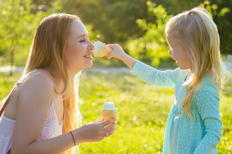 Cute little blonde girl daughter eating vanilla ice cream together with a beautiful mother in the park stock photography