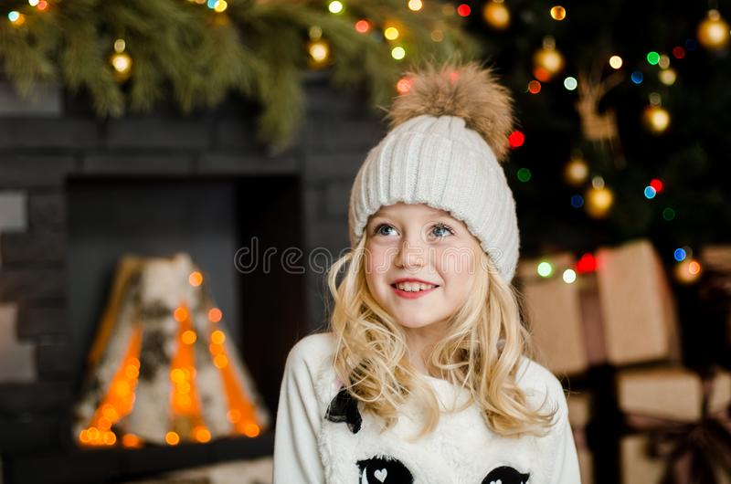 Cute little blonde girl having a gift in her hands on a christmas background. Happy family concept. Cute little blonde girl having a gift in her hands on a stock photography