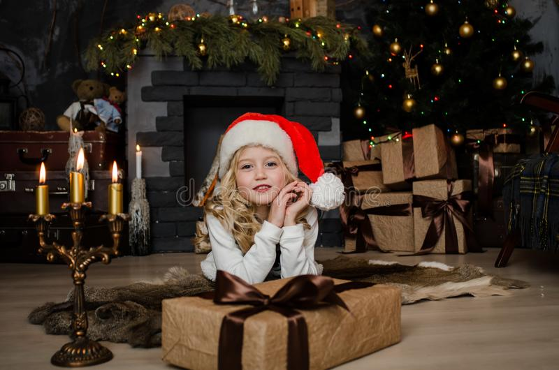 Cute little blonde girl having a gift in her hands on a christmas background. Happy family concept. royalty free stock images