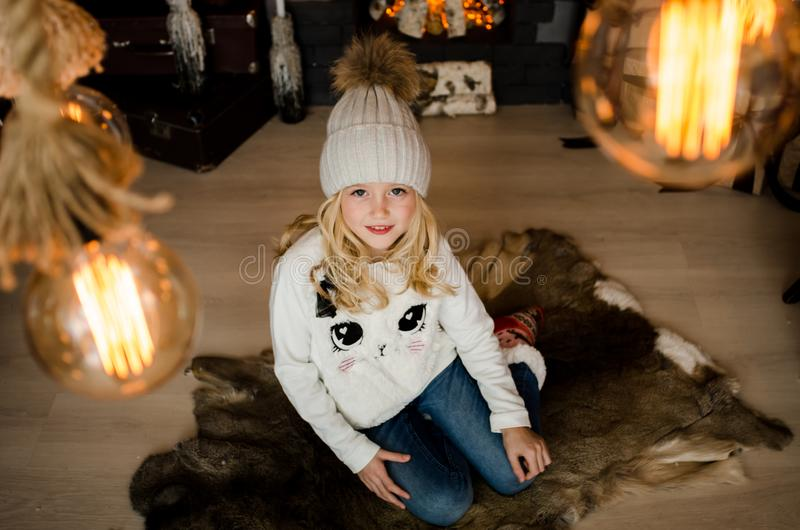 Cute little blonde girl having a gift in her hands on a christmas background. Happy family concept. Cute little blonde girl having a gift in her hands on a stock photos