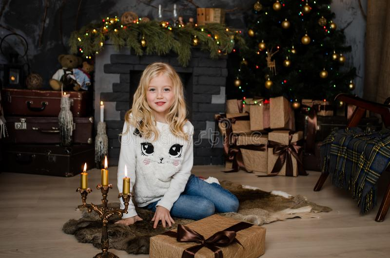Cute little blonde girl having a gift in her hands on a christmas background. Happy family concept. Cute little blonde girl having a gift in her hands on a royalty free stock image