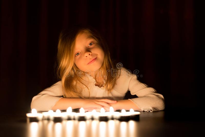 The cute little blonde girl is sitting around lots of burning candle, over dark background. royalty free stock photos
