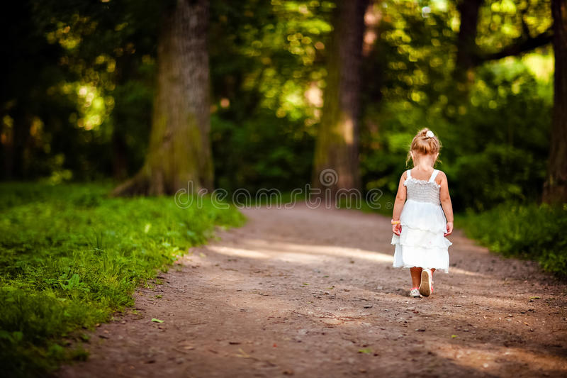 Cute little blonde girl in a white dress walking down the path i stock photos