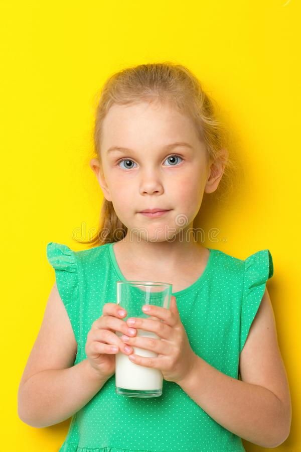Cute kid drinking milk on blue background stock photography