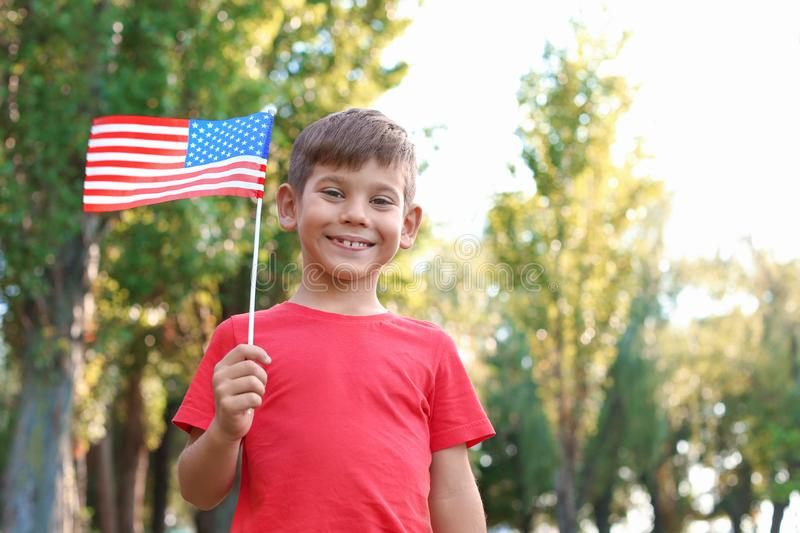 Cute little boy with American flag. In park stock image