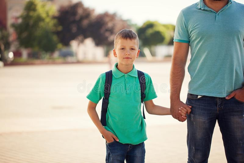 Cute little boy with backpack going to school with his father. royalty free stock image