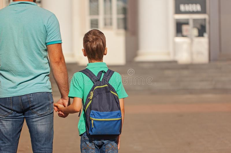 Cute little boy with backpack going to school with his father. Back view. royalty free stock photography