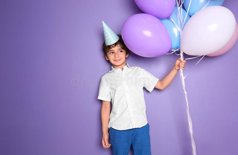 Cute little boy with balloons on color background. Birthday celebration stock photography