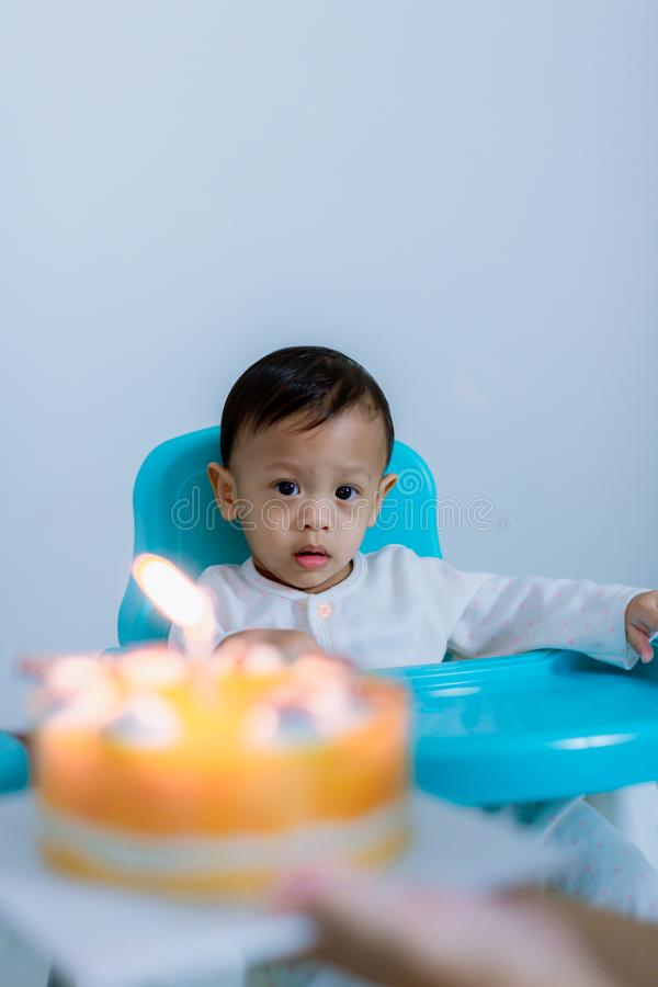Cute little boy with birthday cake sitting on chair in room . stock images