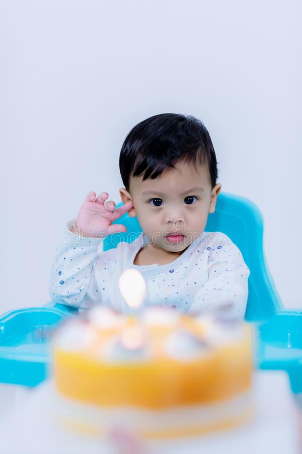Cute little boy with birthday cake sitting on chair in room . stock photos