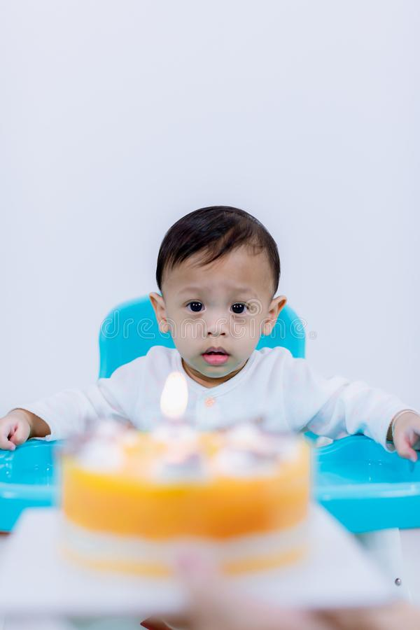 Cute little boy with birthday cake sitting on chair in room . stock image