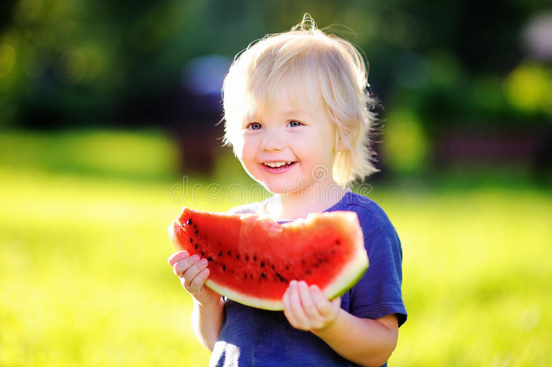 Cute little boy with blond hairs eating fresh watermelon stock photography