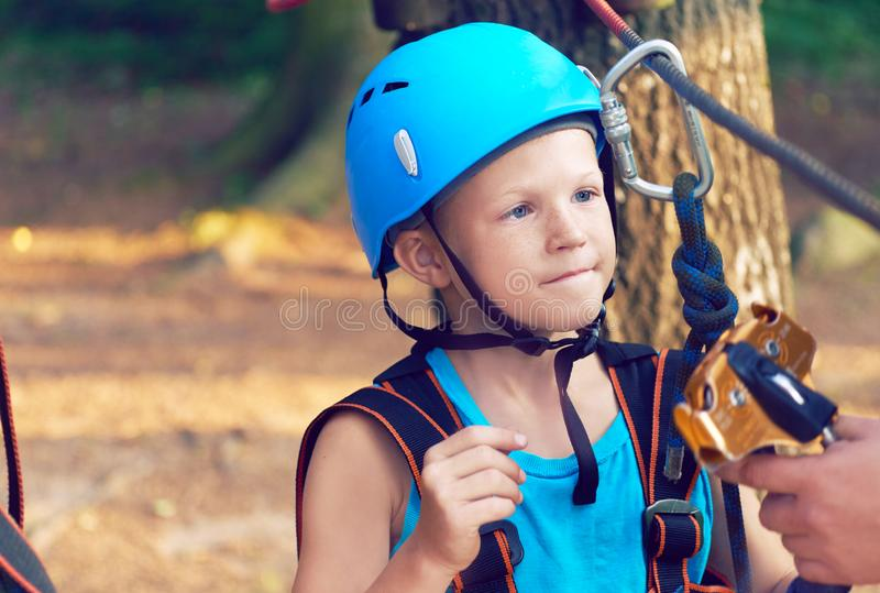Cute little boy in blue shirt and helmet having fun at the adventure park, holding ropes and prepering to climb wooden. Little boy in climbing equipment and a royalty free stock image