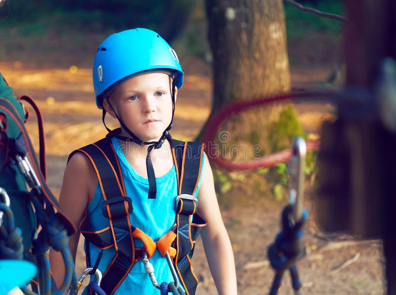 Cute little boy in blue shirt and helmet having fun at the adventure park, holding ropes and prepering to climb wooden. Little boy in climbing equipment and a stock photo