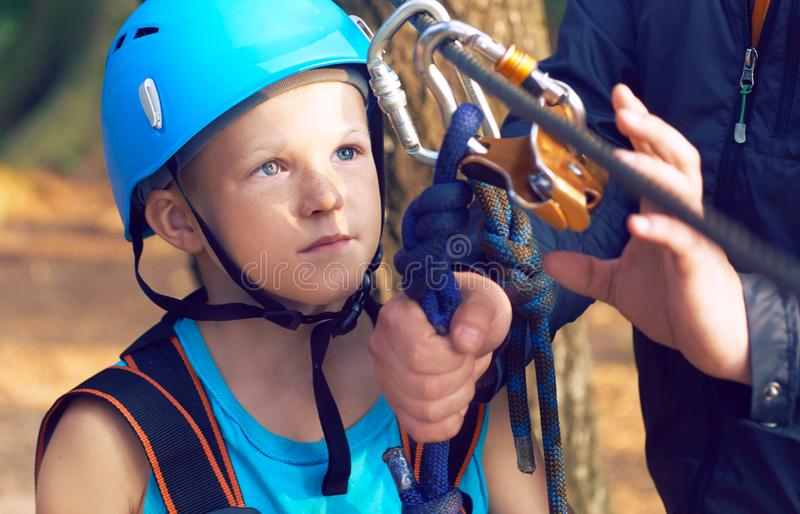 Cute little boy in blue shirt and helmet having fun at the adventure park, holding ropes and prepering to climb wooden. Little boy in climbing equipment and a stock photos