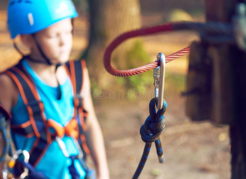 Cute little boy in blue shirt and helmet having fun at the adventure park, holding ropes and prepering to climb wooden stock images