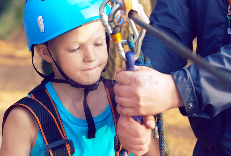 Cute little boy in blue shirt and helmet having fun at the adventure park, holding ropes and prepering to climb wooden. Little boy in climbing equipment and a stock images