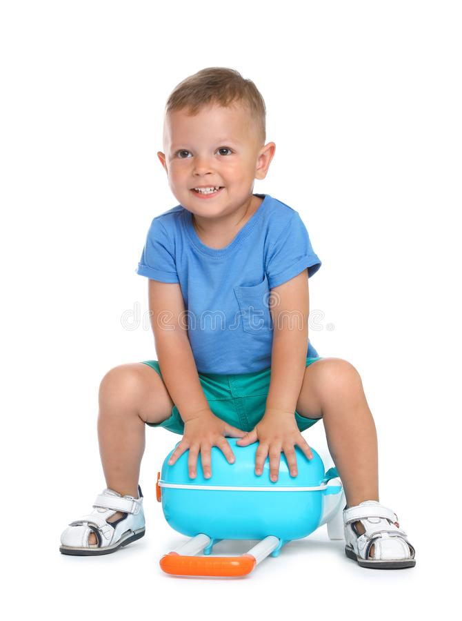 Cute little boy with blue suitcase on white royalty free stock photo