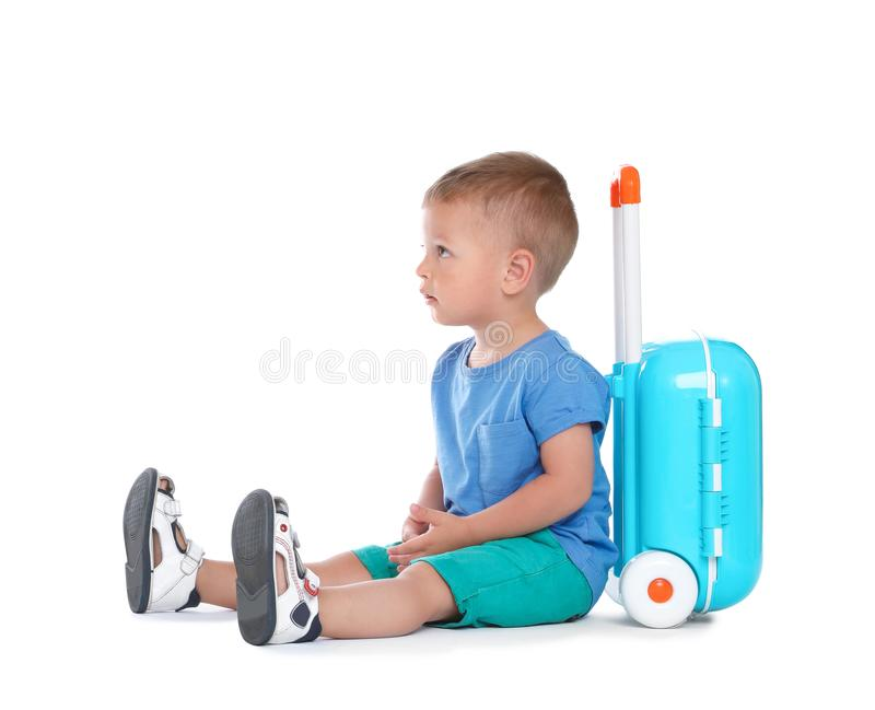 Cute little boy with blue suitcase on white stock photo