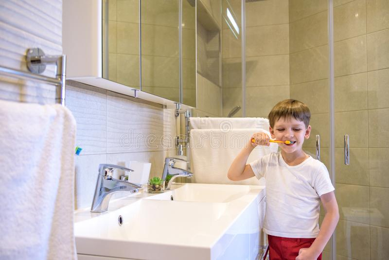 A cute little boy is brushing his teeth with a toothbrush. On a pure white T-shirt in which he is dressed you can make an stock photo