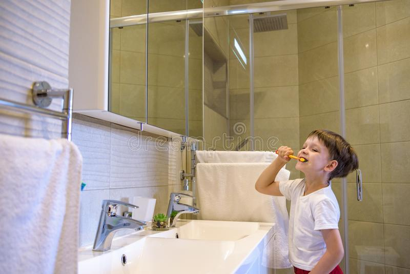 A cute little boy is brushing his teeth with a toothbrush. On a pure white T-shirt in which he is dressed you can make an stock photography