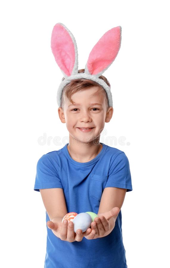 Cute little boy with bunny ears holding Easter eggs on white background royalty free stock photography