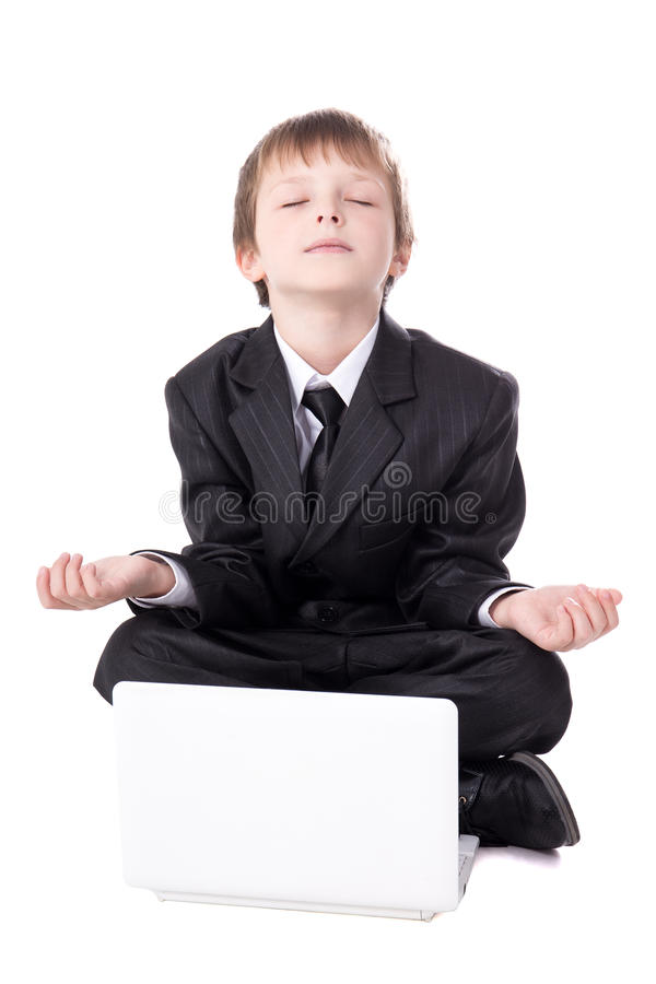cute little boy in business suit sitting in yoga pose with laptop isolated on white royalty free stock images