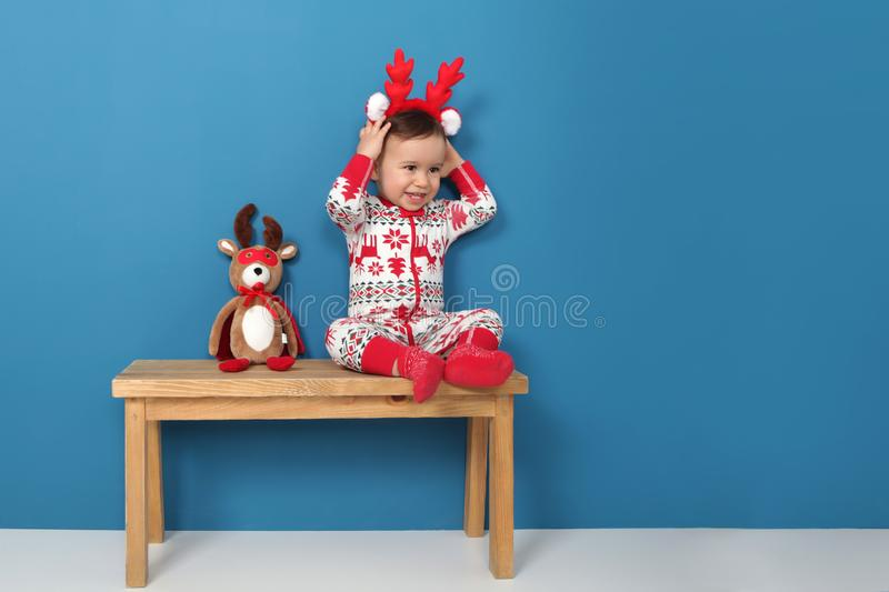 Cute little boy in Christmas pajamas sitting on a bench stock photo