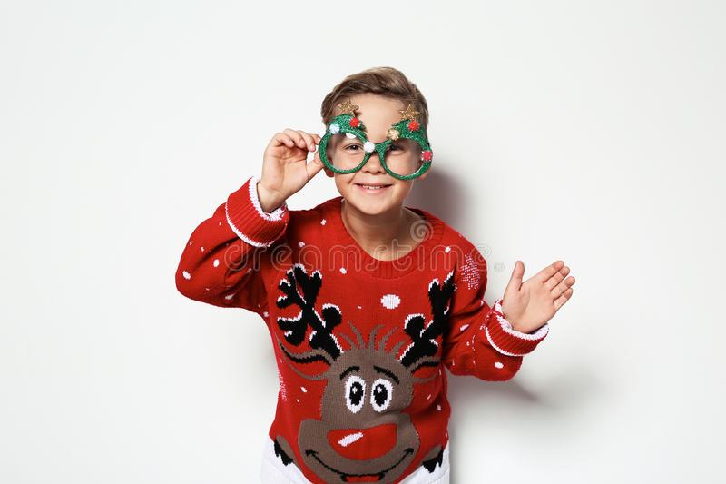 Cute little boy in Christmas sweater with party glasses stock images