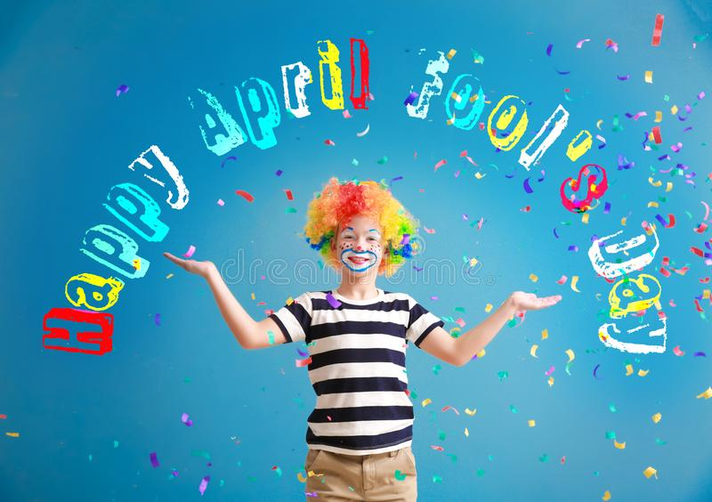 Cute little boy with clown makeup and falling confetti on color background. April fools\' day celebration royalty free stock photo